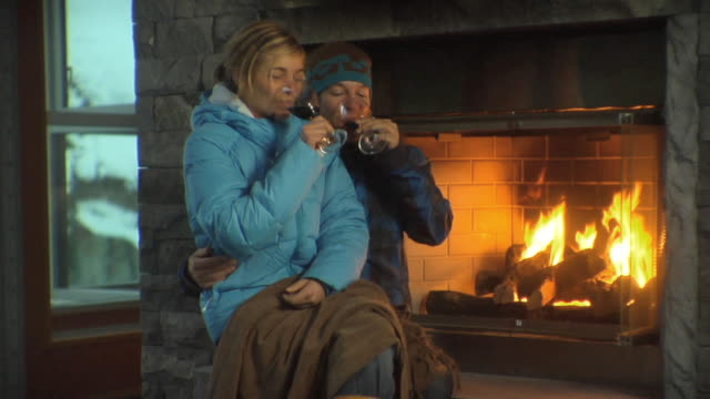 MS Woman sitting on man's lap beside fireplace and having drink / Whistler, British Columbia, Canada