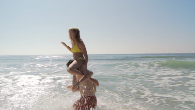 slo mo of woman sitting on mans shoulders in the water at the beach and then falling over - swimming shorts stock videos & royalty-free footage