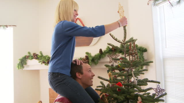 Woman sitting on mans shoulders puts star on top of Christmas tree / Bellevue, Idaho, United States