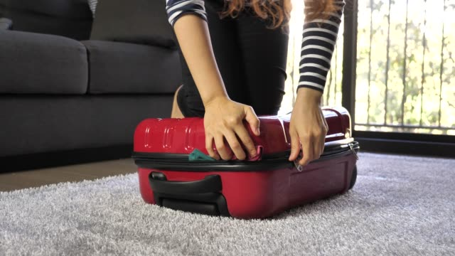 woman sitting on overfilled suitcase - bagaglio video stock e b–roll