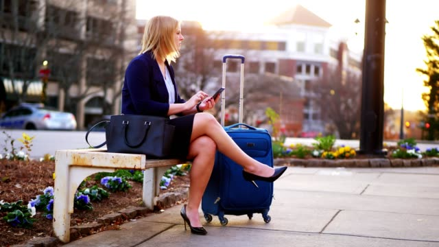 woman sitting on park bench using phone. - business travel stock videos & royalty-free footage