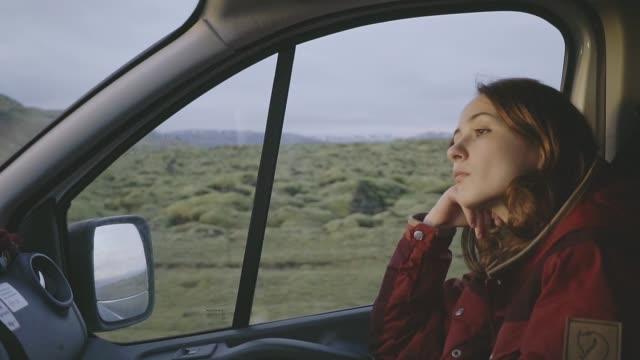 Woman sitting on passenger seat in  camper van