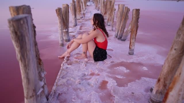 donna seduta sul lago salato rosa in ucraina - colore brillante video stock e b–roll