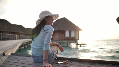 woman sitting on resort and enjoying view at sunset - french overseas territory stock videos & royalty-free footage