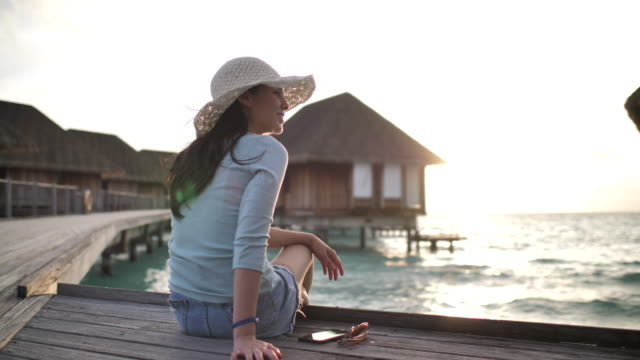 Woman sitting on resort and enjoying view at sunset