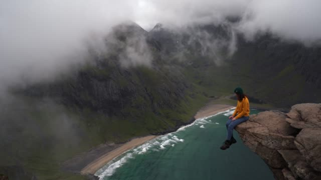 woman sitting on rock and looking at beach on lofoten island - traditionally norwegian stock videos & royalty-free footage