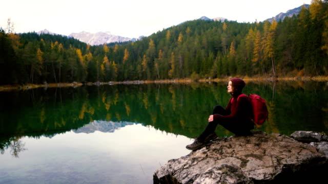 woman sitting on rock and looking  at scenic view of eibsee  lake in alps - baviera video stock e b–roll