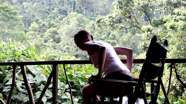 woman sitting on rocking chair watching the rainforest - rocking chair stock videos and b-roll footage