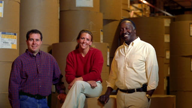 ms portrait woman sitting on rolls with black man + man smiling at camera in warehouse - female with group of males stock videos & royalty-free footage