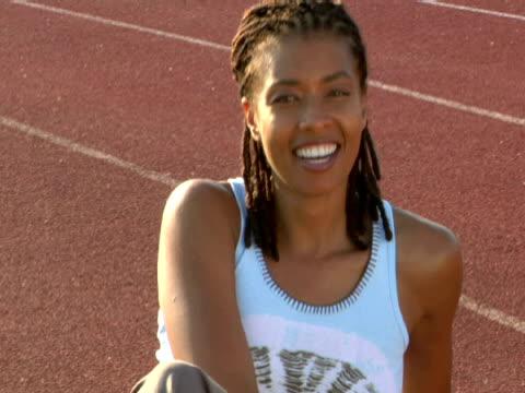 vídeos y material grabado en eventos de stock de cu,  woman sitting on running track,  smiling,  portrait,  miami,  florida,  usa - mano en la barbilla