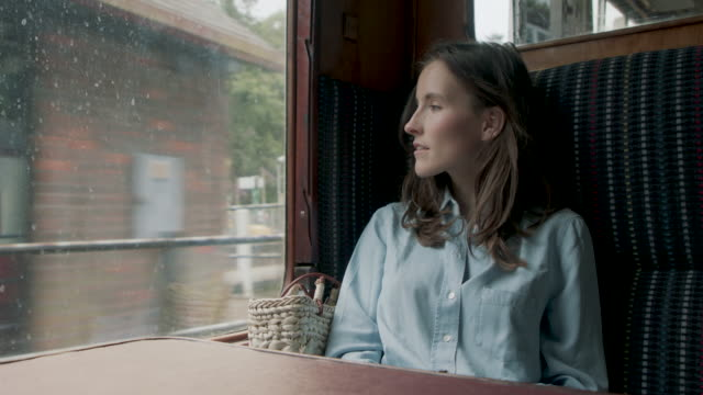 woman sitting on seat in train - table top view video stock e b–roll