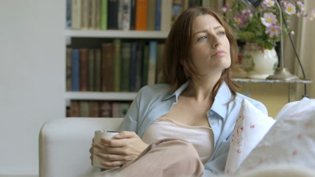 Woman sitting on sofa and drinking coffee.