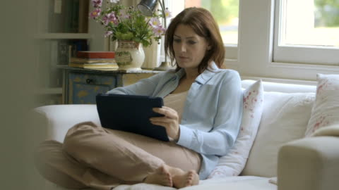 woman sitting on sofa and using digital tablet. - one mid adult woman only stock videos & royalty-free footage