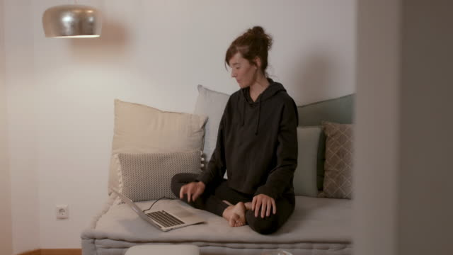 stockvideo's en b-roll-footage met woman sitting on sofa at home looking at laptop - preventie