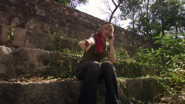 vídeos de stock e filmes b-roll de la ms woman sitting on steps at mayan ruins, talking on cell phone and gesturing / merida, mexico  - braço humano