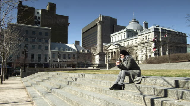 ws woman sitting on steps of montreal city hall drinking coffee with palais de justice de montréal in background / montreal, quebec, canada - ケベックの旗点の映像素材/bロール