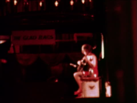 1969 blurred woman sitting on stool playing guitar in nightclub / greenwich village, nyc - greenwich village stock videos & royalty-free footage
