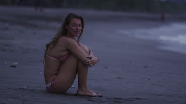 woman sitting on the beach looking at the camera