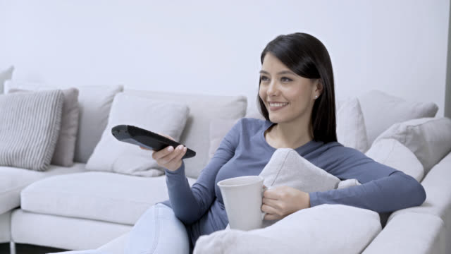 Woman sitting on the couch watching TV drinking coffee