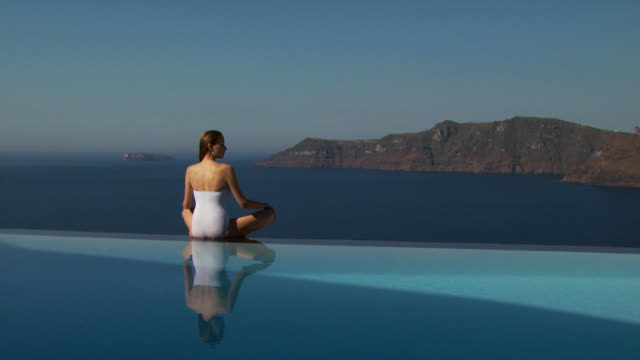 A woman sitting on the edge of an infinity pool