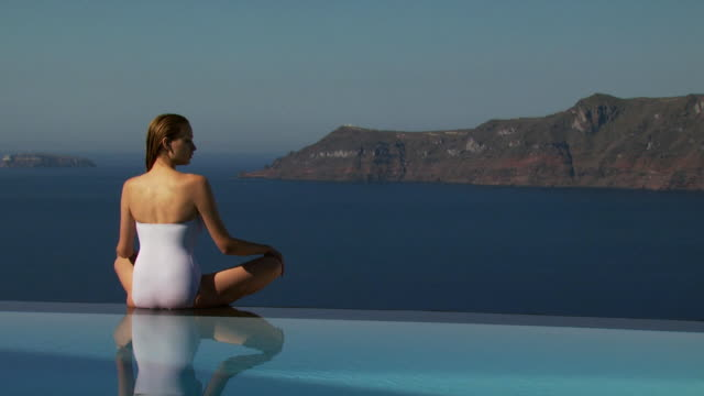 a woman sitting on the edge of an infinity pool - see other clips from this shoot 1144 stock videos & royalty-free footage