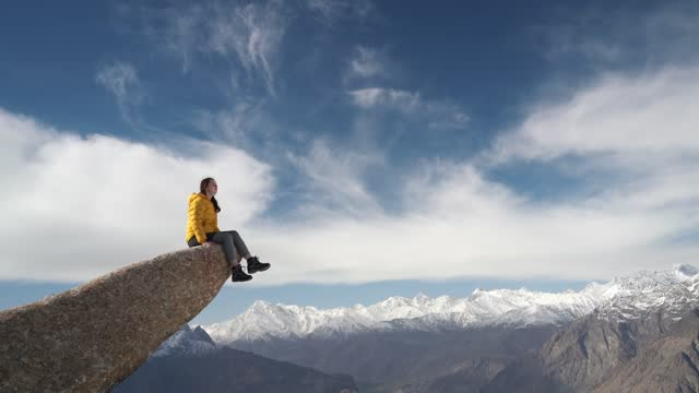 woman sitting on the edge of hanging rock above the river - sitting stock videos & royalty-free footage