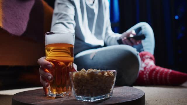 stockvideo's en b-roll-footage met de zitting van de vrouw op de vloer, het letten op tv en het hebben van bier en pinda's - alleen één oudere vrouw