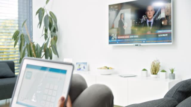 vídeos y material grabado en eventos de stock de ds mujer sentada en el sofá y usando su aplicación casa inteligente en la tableta para encender el televisor - accesibilidad