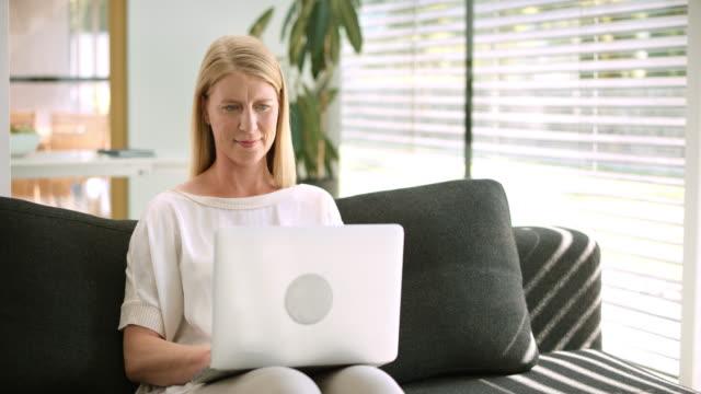ソファーに座って、彼女のラップトップに取り組んで ds 女性 - 操作する点の映像素材/bロール