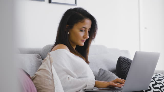 woman sitting on the sofa with her laptop - sweden stock videos & royalty-free footage
