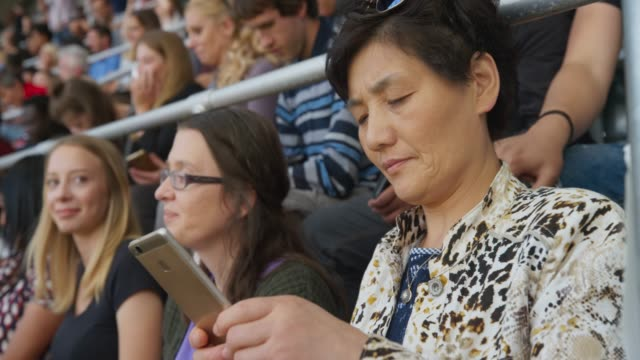 woman sitting on the stadium tribune and taking photos before the event - fan enthusiast stock videos & royalty-free footage