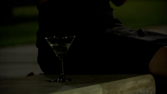 stockvideo's en b-roll-footage met a woman sitting on the the edge of a swimming pool drinks a martini and answers her cell phone. - aanbellen
