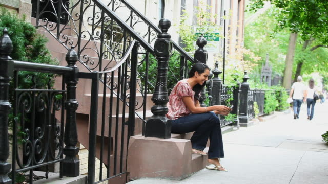 woman sitting on urban staircase texting on cell phone - front stoop stock videos and b-roll footage