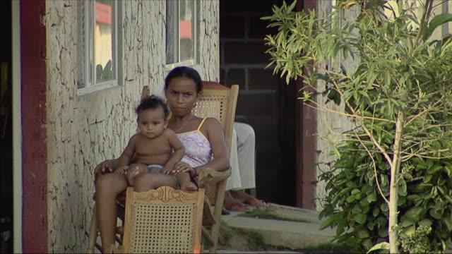 vídeos y material grabado en eventos de stock de ms woman sitting on wheelchair with child / colombia - en el regazo