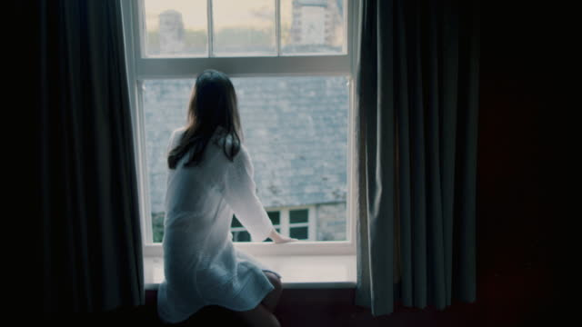 vidéos et rushes de woman sitting on window sill in night shirt in morning - personne sereine