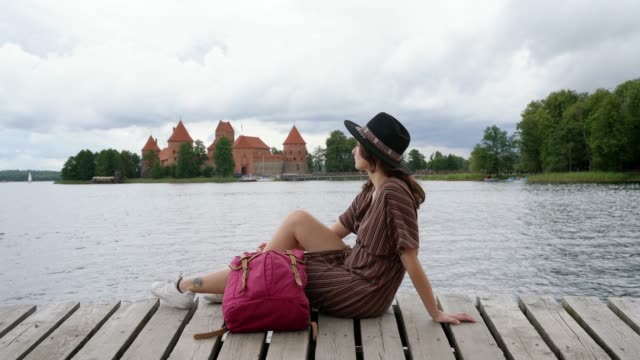 woman sitting on wooden pier near trakai castle - lithuania stock videos & royalty-free footage
