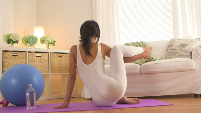 woman sitting on yoga mat in living room stretching legs - gymnastikanzug stock-videos und b-roll-filmmaterial