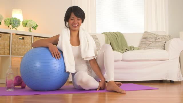 vídeos de stock e filmes b-roll de woman sitting on yoga mat in living room - body de ginástica