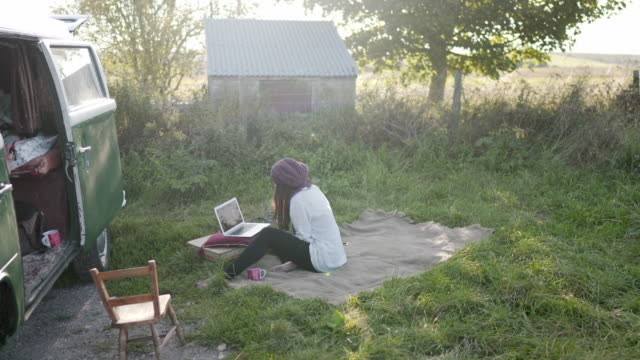 stockvideo's en b-roll-footage met a woman sitting out side on the grass in a field next to a van remote working - buiten de vs