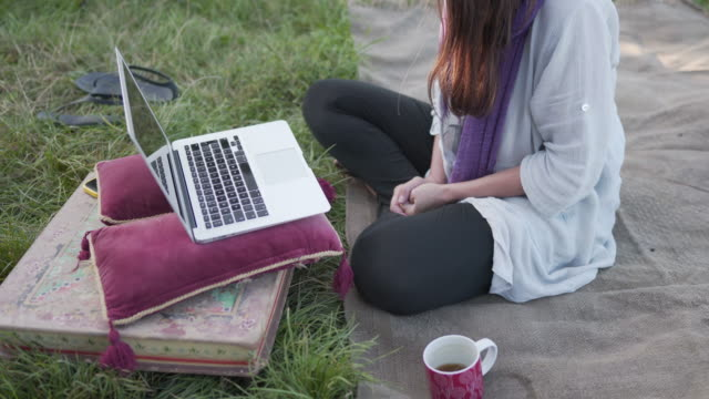 a woman sitting out side on the grass in a field remote working - non us film location stock videos & royalty-free footage