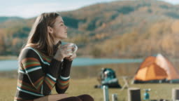 Woman sitting, reading book and drinking coffee on camping trip by the lake