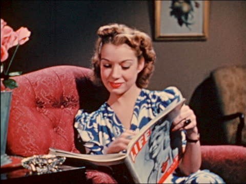 1941 woman sitting + reading life magazine + smiling / industrial - zeitschrift stock-videos und b-roll-filmmaterial