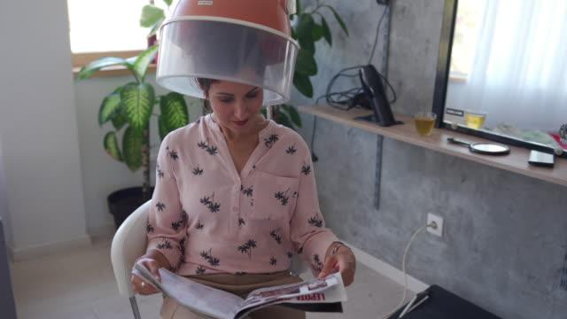 vídeos y material grabado en eventos de stock de mujer sentada bajo secador de pelo en salón de belleza - magazine