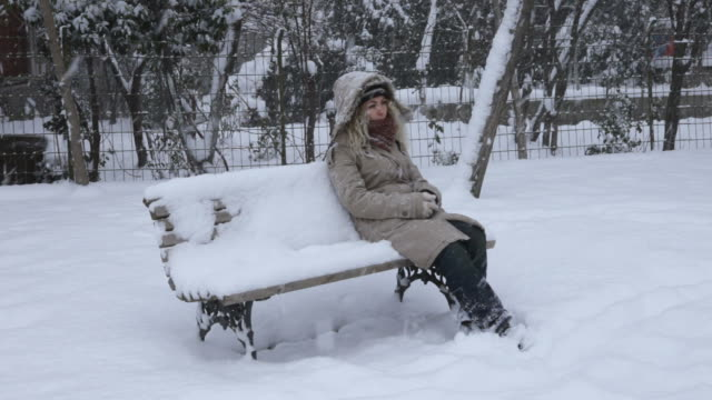 Woman sitting under the snowstorm