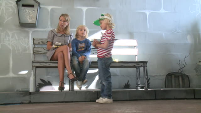 ms woman sitting with boy (8-9) on stage set bench while other boy (6-7) jumping next to them, gent, belgium - sun visor stock videos and b-roll footage