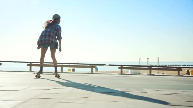Woman skateboarding at beach