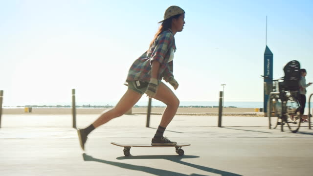frau am strand skateboarding - skateboard stock-videos und b-roll-filmmaterial