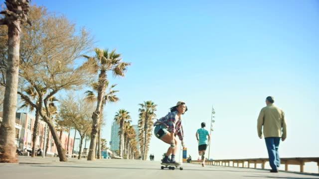 vídeos de stock e filmes b-roll de woman skateboarding at beach - barcelona espanha