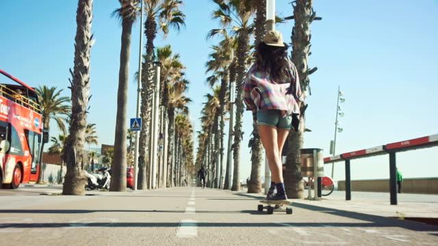 vídeos de stock, filmes e b-roll de mulher andando de skate em praia - andar de skate