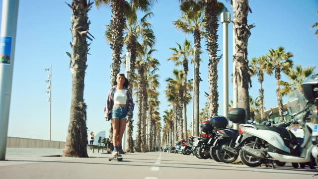 woman skateboarding at beach - promenade stock videos & royalty-free footage